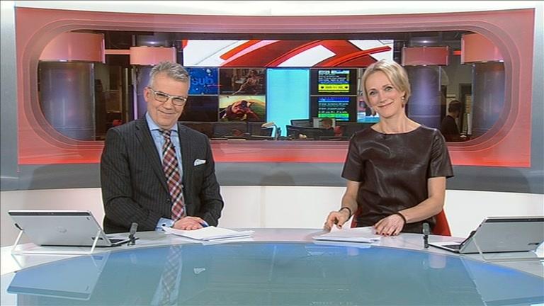 Maija Lehmusvirta ruskeassa nahkamekossa juontamassa uutislähetystä.